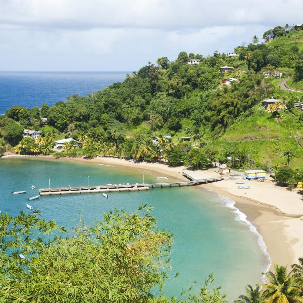 An overview of Parlatuvier Bay and its jetty on Tobago's north coast showing the blue water of the Caribbean Sea and the aqua water in the Bay.